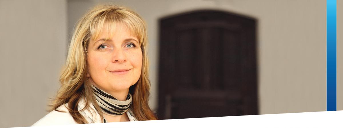Porträt einer blonden Frau mit weißer Lederjacke und schwarz-weiß gestreiftem Schal