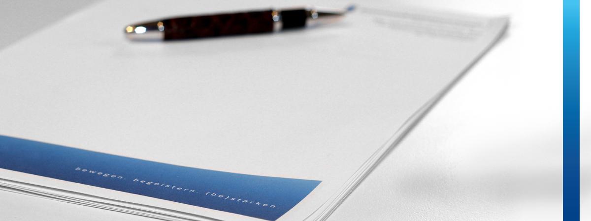 """Füllfeder liegt auf weißem Briefpapier mit blauem Balken und Text """"bewegen, begeistern, bestärken"""""""