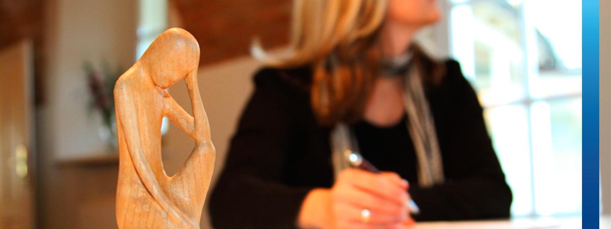 Frau schaut nachdenklich zum Fenster raus, auf Schreibtisch steht eine Holzfigur in Form eines denkenden Menschen