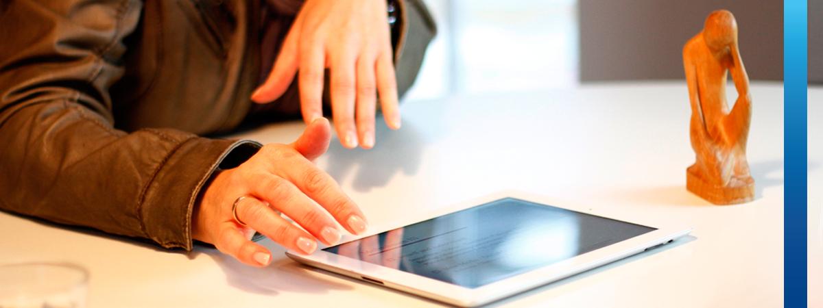 Frau zeigt einer anderen Person etwas mit einem Tablet-PC auf einem Besprechungstisch