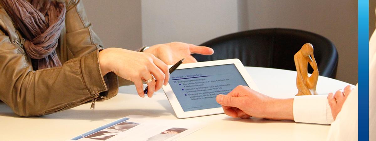 Zwei Personen in Besprechung, Frau zeigt auf Tablet-PC auf dem Tisch