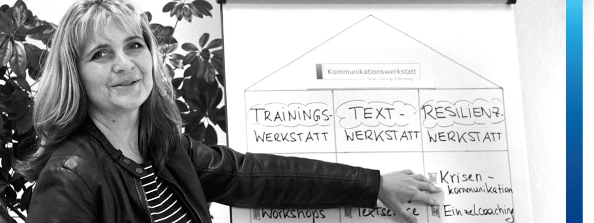 Frau zeigt auf Flipchart mit dem Text Trainingswerkstatt, Textwerkstatt , Resilienzwerkstatt und Krisenkommunikation