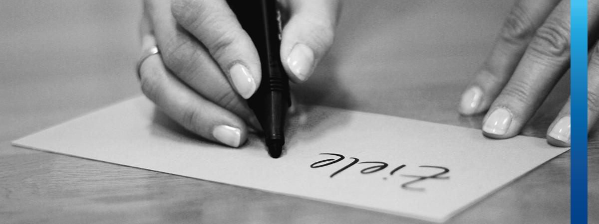 Schwarz-weißes Bild, Frau schreibt auf Moderationskarte den Text Ziele